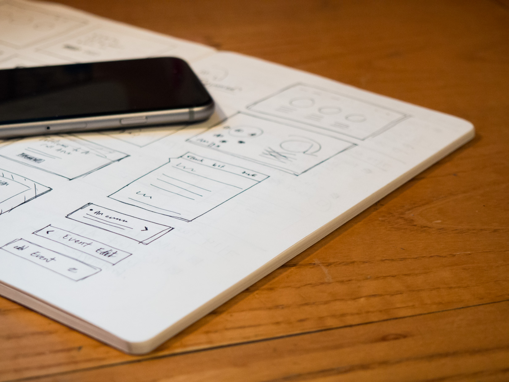 Notebook with Sketches and Phone on Desk