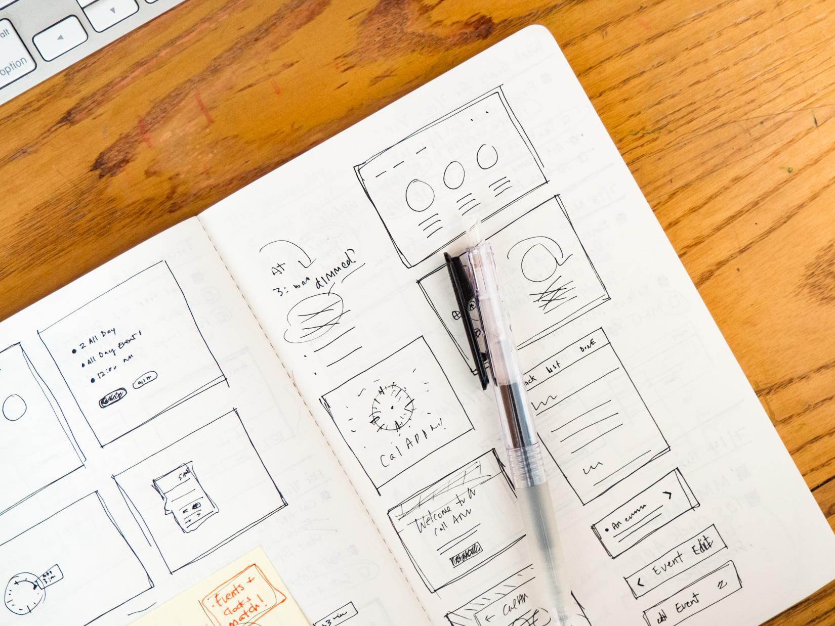 Sketchbook and Pen on Wooden Desk