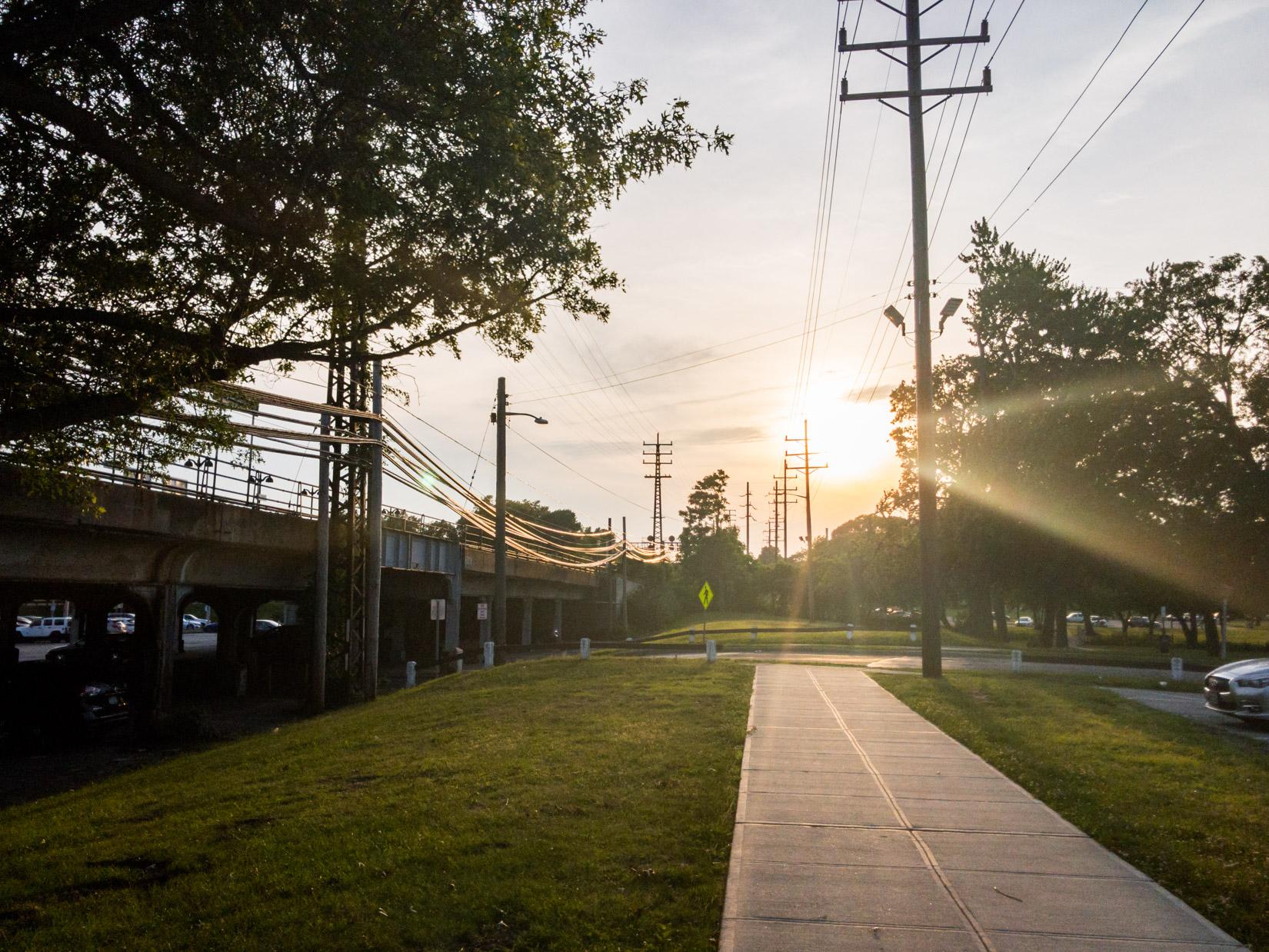 Sun Above Sidewalk and Train Station
